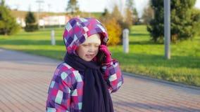 6χρονο κορίτσι σε ένα σακάκι και ένα καπέλο που μιλούν στο τηλέφωνο στο πάρκο φιλμ μικρού μήκους