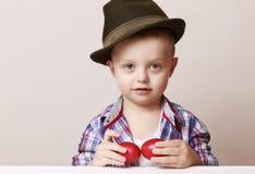 4χρονο μικρό και χαριτωμένο αγόρι στα χέρια εκμετάλλευσης καπέλων και πουκάμισων Στοκ Εικόνες