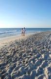 Χρονολογώντας το ζεύγος που περπατά μαζί σε μια ηλιόλουστη παραλία Στοκ Φωτογραφίες