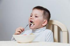 4χρονο παιδί σε ένα άσπρο turtleneck που τρώει τα ζυμαρικά με ένα δίκρανο στον πίνακα στοκ φωτογραφία