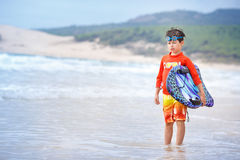 Χρονών αγόρι έξι με τον πίνακα κυματωγών στην εξωτική παραλία Στοκ Εικόνες