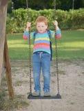 5 χρονών κοκκινομάλλες ευτυχές αγόρι με την ταλάντευση σακιδίων πλάτης του που στέκονται κατακόρυφα και την αφηρημάδα στοκ εικόνες
