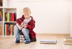 Χρονών συνεδρίαση παιδιών τρία μεταξύ των βιβλίων στο σπίτι στοκ εικόνες