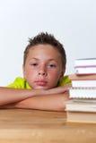 12 χρονών συνεδρίαση αγοριών στον πίνακα με τα βιβλία Στοκ Φωτογραφία