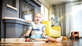 Χρονών το αγόρι δύο παίζει με τα παιχνίδια του στο εσωτερικό στοκ φωτογραφίες
