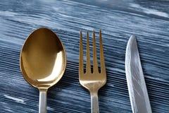 Χρυσά δίκρανο και μαχαίρι κουταλιών στο γκρίζο ξύλινο υπόβαθρο το αναδρομικό επιτραπέζιο σκεύος κουζινών ύφους με τις γρατσουνιές Στοκ εικόνα με δικαίωμα ελεύθερης χρήσης