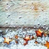 Χρυσά αστέρια με το χιόνι σε ένα αγροτικό υπόβαθρο Χριστουγέννων Στοκ εικόνα με δικαίωμα ελεύθερης χρήσης
