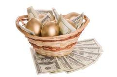 Χρυσά αυγά και δολάρια σε ένα καλάθι που απομονώνεται Στοκ Φωτογραφία