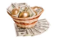 Χρυσά αυγά και δολάρια σε ένα καλάθι που απομονώνεται Στοκ εικόνα με δικαίωμα ελεύθερης χρήσης