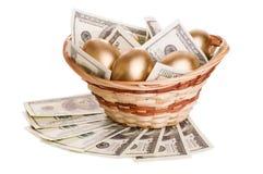 Χρυσά αυγά και δολάρια σε ένα καλάθι που απομονώνεται Στοκ εικόνες με δικαίωμα ελεύθερης χρήσης