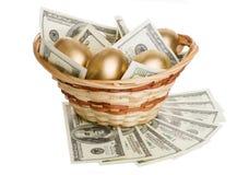 Χρυσά αυγά και δολάρια σε ένα καλάθι που απομονώνεται Στοκ Εικόνα