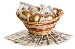Χρυσά αυγά και δολάρια σε ένα καλάθι Στοκ εικόνες με δικαίωμα ελεύθερης χρήσης