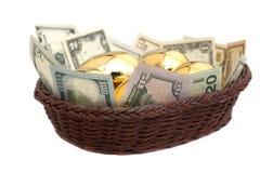 Χρυσά αυγά και δολάρια στο καλάθι που απομονώνεται στο λευκό Στοκ Φωτογραφίες