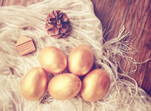 Χρυσά αυγά Πάσχας και διακοσμημένος στο ξύλινο υπόβαθρο στοκ εικόνα με δικαίωμα ελεύθερης χρήσης