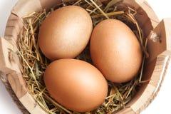 Χρυσά αυγά σε ένα ξύλινο καλάθι Πάσχα Στοκ Εικόνα