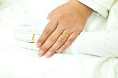 Χρυσά δαχτυλίδια στα δάχτυλα δαχτυλιδιών νεόνυμφων και της νύφης Στοκ Φωτογραφίες