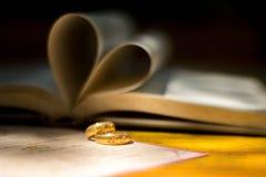 Χρυσά γαμήλια δαχτυλίδια, βιβλίο καρδιών, θαμπάδα υποβάθρου Στοκ Φωτογραφία