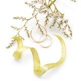 Χρυσά γαμήλια δαχτυλίδια και λουλούδια κλάδων Στοκ εικόνα με δικαίωμα ελεύθερης χρήσης