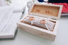 Χρυσά γαμήλια δαχτυλίδια σε ένα άσπρο ξύλινο κιβώτιο γάμος κορδελλών πρόσκλησης λουλουδιών κομψότητας λεπτομέρειας διακοσμήσεων α Στοκ Εικόνες