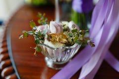Χρυσά γαμήλια δαχτυλίδια σε ένα βάζο κρυστάλλου με τα φρέσκα λουλούδια Χρυσά γαμήλια δαχτυλίδια σε ένα βάζο γυαλιού σε ένα εκλεκτ στοκ φωτογραφίες