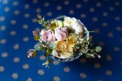 Χρυσά γαμήλια δαχτυλίδια σε ένα βάζο κρυστάλλου με τα φρέσκα λουλούδια Χρυσά γαμήλια δαχτυλίδια σε ένα βάζο γυαλιού σε ένα εκλεκτ στοκ εικόνες