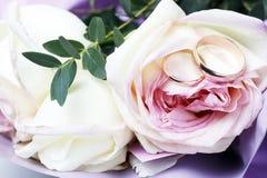 Χρυσά γαμήλια δαχτυλίδια σε μια ανθοδέσμη των τριαντάφυλλων, γαμήλια έννοια στοκ φωτογραφίες με δικαίωμα ελεύθερης χρήσης