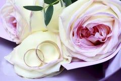 Χρυσά γαμήλια δαχτυλίδια σε μια ανθοδέσμη των τριαντάφυλλων, γαμήλια έννοια στοκ εικόνες
