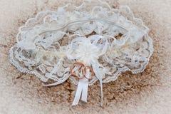 Χρυσά γαμήλια δαχτυλίδια σε μια garters υποβάθρου νύφη στην ημέρα Στοκ Φωτογραφία