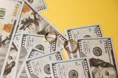 Χρυσά γαμήλια δαχτυλίδια στο υπόβαθρο λογαριασμών δολαρίων Έννοια διαζυγίου ή απιστίας στοκ φωτογραφία
