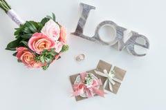 Χρυσά γαμήλια δαχτυλίδια, διακοσμητικοί φάκελοι, όμορφα ανθοδέσμη και σύμβολο αγάπης Στοκ εικόνα με δικαίωμα ελεύθερης χρήσης