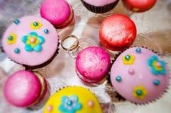 Χρυσά γαμήλια δαχτυλίδια μεταξύ των ζωηρόχρωμων cupcakes στο πιάτο γυαλιού Στοκ Εικόνα