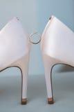 Χρυσά γαμήλια δαχτυλίδια μεταξύ των παπουτσιών Στοκ εικόνα με δικαίωμα ελεύθερης χρήσης