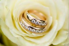 Χρυσά γαμήλια δαχτυλίδια με τα διαμάντια στα ροδαλά πέταλα Στοκ φωτογραφία με δικαίωμα ελεύθερης χρήσης