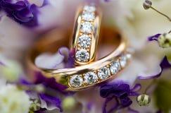 Χρυσά γαμήλια δαχτυλίδια με τα διαμάντια στη γαμήλια ανθοδέσμη των ιωδών λουλουδιών Στοκ Φωτογραφίες