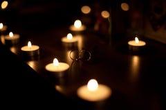 Χρυσά γαμήλια δαχτυλίδια με τα κεριά Στοκ Εικόνες