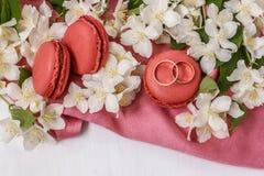 Χρυσά γαμήλια δαχτυλίδια με τα λουλούδια η άσπρη Jasmine, macaroons και το ρόδινο drape Στοκ Εικόνες