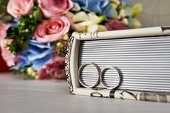 Χρυσά γαμήλια δαχτυλίδια, λουλούδια λευκωμάτων βιβλίων fnd Στοκ φωτογραφία με δικαίωμα ελεύθερης χρήσης