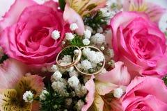 Χρυσά γαμήλια δαχτυλίδια σε ένα υπόβαθρο λουλουδιών Στοκ Εικόνες