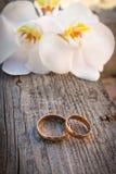 Χρυσά γαμήλια δαχτυλίδια σε μια ανθοδέσμη των άσπρων ορχιδεών Στοκ φωτογραφίες με δικαίωμα ελεύθερης χρήσης