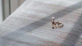 Χρυσά γαμήλια δαχτυλίδια σε μια επιτραπέζια κινηματογράφηση σε πρώτο πλάνο απόθεμα βίντεο