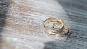 Χρυσά γαμήλια δαχτυλίδια σε μια επιτραπέζια κινηματογράφηση σε πρώτο πλάνο φιλμ μικρού μήκους