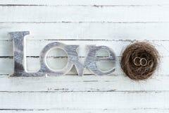 Χρυσά γαμήλια δαχτυλίδια στη φωλιά και σύμβολο αγάπης ξύλινο tabletop Στοκ Εικόνες