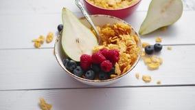 Χρυσά δημητριακά με τους νωπούς καρπούς των σμέουρων, των βακκινίων και του αχλαδιού στο κεραμικό κύπελλο φιλμ μικρού μήκους