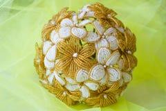 Χρυσά και άσπρα λουλούδια γαμήλιων ανθοδεσμών από τις χάντρες Σε ένα κίτρινο θολωμένο υπόβαθρο στοκ εικόνες με δικαίωμα ελεύθερης χρήσης