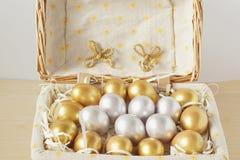 Χρυσά και ασημένια αυγά που γεννιούνται σε ένα καλάθι Στοκ εικόνα με δικαίωμα ελεύθερης χρήσης
