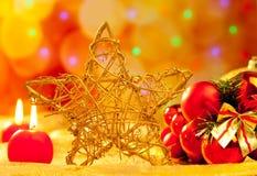 Χρυσά κεριά και μπιχλιμπίδια αστεριών Χριστουγέννων Στοκ Φωτογραφίες