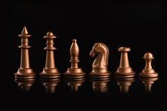 χρυσά κομμάτια σκακιού στο Μαύρο στιλπνό Στοκ φωτογραφία με δικαίωμα ελεύθερης χρήσης