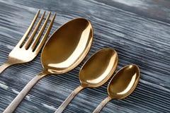 Χρυσά κουτάλια και δίκρανο στο γκρίζο ξύλινο υπόβαθρο το εκλεκτής ποιότητας επιτραπέζιο σκεύος με τις γρατσουνιές ξύνει στρέψτε μ Στοκ Φωτογραφία