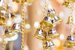 χρυσά κουδούνια Χριστουγέννων που κρεμούν ως νέα παιχνίδια και δώρο έτους Στοκ Εικόνα