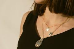 χρυσά κρεμαστά κοσμήματα γύρω από το λαιμό ενός κοριτσιού στον ήλιο μοντέρνο κόσμημα μόδας στο πρόσωπο στοκ φωτογραφία με δικαίωμα ελεύθερης χρήσης
